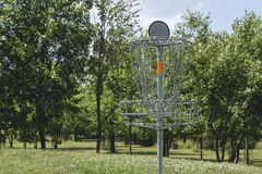 Golf basket on a course in front of trees Royalty Free Stock Photography