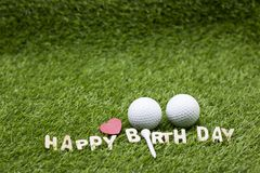 Golf ball with Happy birthday sign on green grass Royalty Free Stock Image