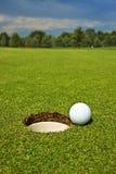 Golf, bola que encontra-se no verde ao lado do furo imagens de stock royalty free