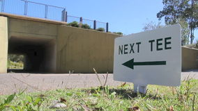 Golf 3. A golf buggy is driven by a next tee sign going into a tunnel stock video