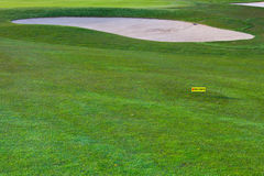 The golf bunker and a directional sign for golf carts Stock Photography