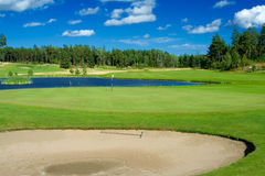 Golf bunker, green, and pond. Swedish golf landscape on a sunny day in July Royalty Free Stock Images