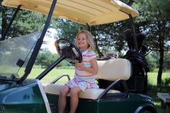 Golf Caddy. A yound girl driving a golf cart Royalty Free Stock Photo