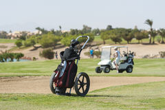 Golf caddy trolley on fairway. Golf caddy trolley and bag on the fairway with buggy  and bunker in the distance Royalty Free Stock Image
