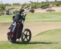 Golf caddy trolley on fairway. Golf caddy trolley and bag on a golf course with bunker in the background Stock Image