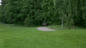 Golf car driving away at a golf course stock footage