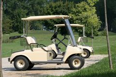 Golf cars. Two white golf car in a golf center Royalty Free Stock Photos