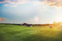 Golf cars on trimmed lawn, game course at sunset Royalty Free Stock Image