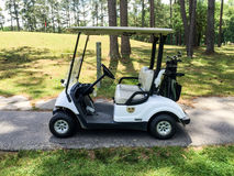 Golf Cart. Golf bag with clubs sits on the back of a golf cart on a golf course stock images