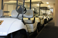 Golf cart buggies at golfing resort. A row of golf cart buggies ready for use at a golfing resort Royalty Free Stock Photo