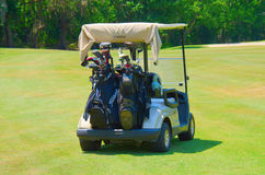 Golf cart with clubs loaded in back. Golf cart with two golf bags loaded with expensive golf clubs Stock Images