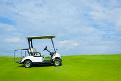Golf cart in golf course and green grass with soft cloud sky Stock Photos