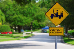 Golf Cart Crossing Sign on Residential Street. Golf Cart Crossing sign on a residential street intersetion with blurred lush green trees in the background Royalty Free Stock Images