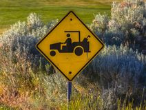 Golf cart crossing sign seen near road stock images