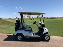 Golf Cart. Golf cart sitting near the golf hole with golfers in the background looking to putt stock photos