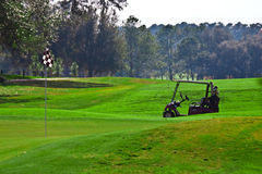 Golf cart on golf course. Golf cart parked near putting green on golf course Royalty Free Stock Photography