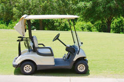Golf cart on a golf course. By a path with a lush forest in the background Stock Images