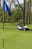 Golf cart and hole pin on the course Royalty Free Stock Photos