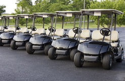 Golf Cart Lineup. Five golf carts lined up waiting for the next golfers.  Black with cream colored upholstery Royalty Free Stock Images