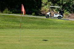 Golf cart next to a hole. On a golf course Royalty Free Stock Image
