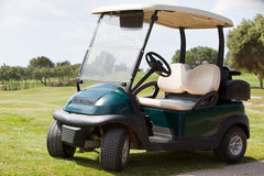 Golf cart parked on a fairway. Empty electric golf cart parked on a fairway at a golf club in the hot summer sunshine stock photos