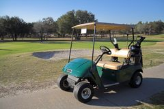 Golf Cart on a Path. Golf Cart empty parked next to a bunker on golf course royalty free stock photos