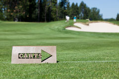 Golf Cart Path Sign. A cut out metal sign tells golf carts when to head back to the path off the green. Background with golfers by the sand trap and hole Stock Photography