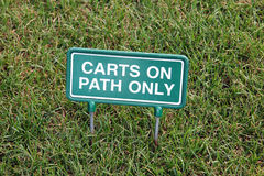 Golf Cart Sign. A sign at a golf course that is in the grass that reads Carts on Path Only Royalty Free Stock Photo