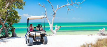 Golf cart at tropical beach. Family driving in golf cart along the tropical beach Stock Photos