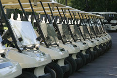 Golf Carts. A row of golf carts are lined up at the starting area and are ready to begin the day's round with a shotgun start tournament stock photo