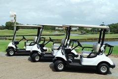 Golf Carts. Three parked white golf carts Royalty Free Stock Photography
