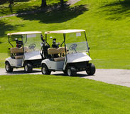 Golf carts. Two empty white golf carts waiting on the green stock images