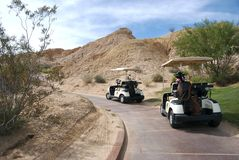 Golf Carts. Sitting on desert golf course path Stock Photo