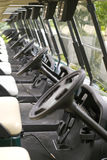 Golf carts. Focus on the second steering wheel Stock Photos