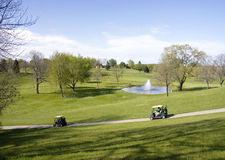 Golf Carts On A Hill. Two golf carts and golfers going down a steep cart path hill Stock Photos