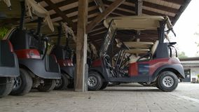 Golf carts parked In the covered wooden place.  stock video footage