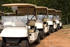 Golf Carts Ready. Brand new golf carts in a nose to tail row waiting to play Stock Photos