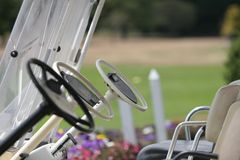 Golf carts at the ready. Three golf carts standing at the ready, on a course in Canterbury, New Zealand.  Very shallow DOF around one of the window frames Royalty Free Stock Photography