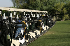 Golf Carts Ready. A row of golf carts are lined up at the starting area and are ready to start the day's round with a shotgun start tournament. The carts are stock photo