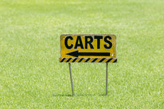 The golf carts sign on a golf field for the direction with blurr. Ed natural green grass on background Royalty Free Stock Photography