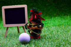 Golf with Christmas ornament on green grass Stock Photos