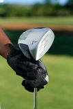 Golf club. A hand with glove holding a golf club Royalty Free Stock Images