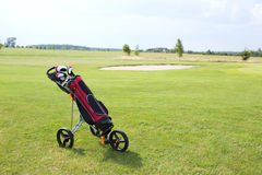 Golf club bag on pushcart at golf course against sky Stock Photos