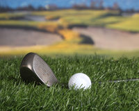 Golf club and ball. Golf club laying on the fairway with sand trap in background Royalty Free Stock Images