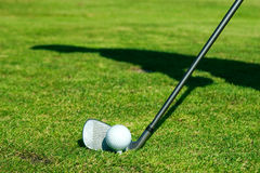 Golf club and ball. Golf ball with club and silhouette of player on the green Stock Photo