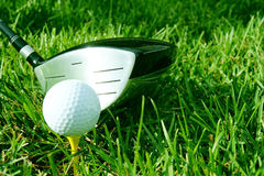 Golf club and ball. Golf club ready to hit the white ball on the yellow tee in green grass Stock Photo