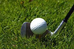Golf club and ball. A golf club ready to strike a golf ball on the grass Stock Image