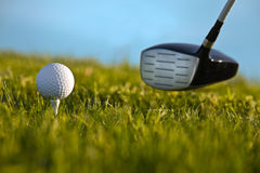 Golf club and ball. Golf club and a golf ball on a tee with green grass and blue sky Royalty Free Stock Images
