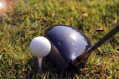 Golf club and golf ball close up in golf coures at Thailand. Blurred golf club and golf ball close up in grass field with sunset. Golf ball close up in golf Royalty Free Stock Photo