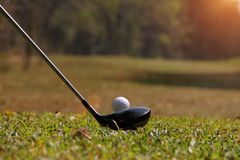 Golf club and golf ball close up in golf coures at Thailand. Blurred golf club and golf ball close up in grass field with sunset. Golf ball close up in golf Royalty Free Stock Photos